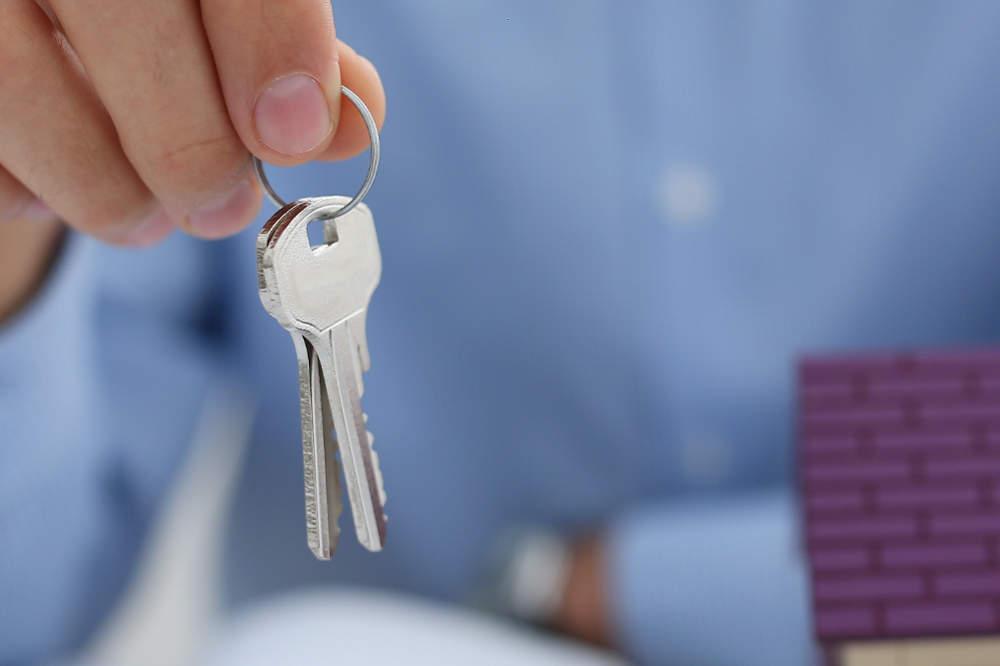 Hand mit Wohnungsschlüssel und Modellhaus - bildlich für Mietrecht