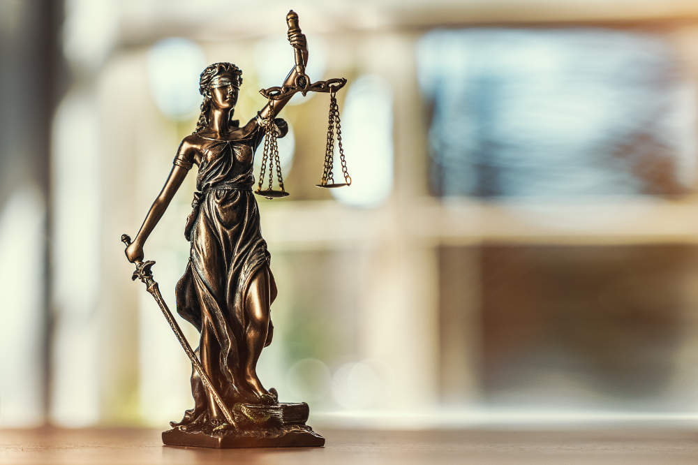 Justicia-Statue auf dem Schreibtisch - bildlich für Strafrecht