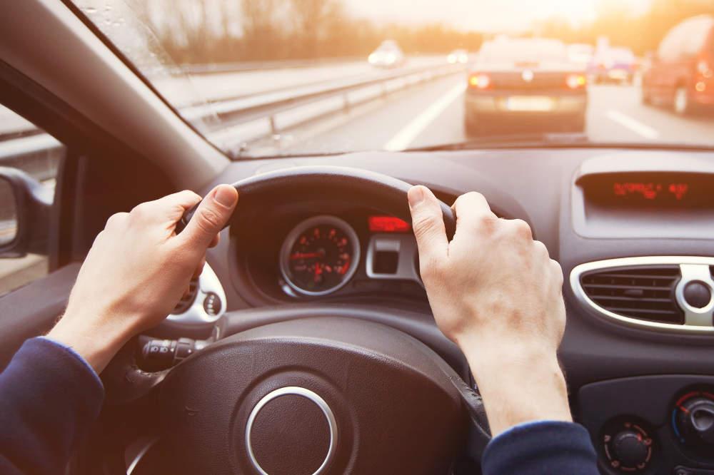 Hände am Steuer im Verkehr - bildlich für Verkehrsrecht