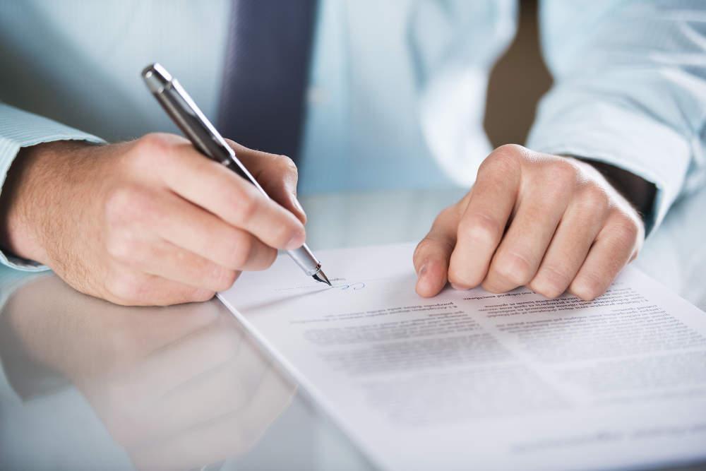 Unterschrift unter einem Vertrag - bildlich für Vertragsrecht